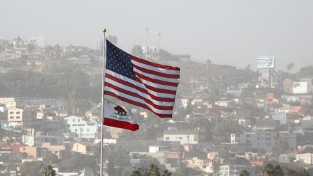 The United States and California State flags fly over Tijuana Mexico at the San Ysidro border crossing in San Diego, California, U.S., November 13, 2018.   REUTERS/Mike Blake