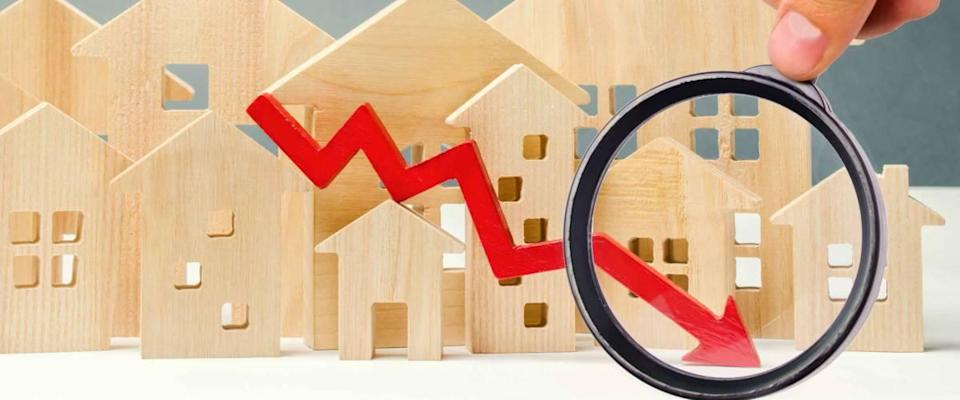 The concept of falling real estate market.  Reduced interest on the mortgage.  Small wooden houses with red arrow down.
