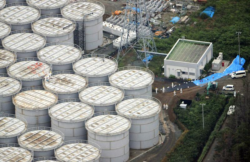 In this Tuesday, Aug. 20, 2013 aerial photo, workers stand on storage tanks at the Fukushima Dai-ichi nuclear plant at Okuma in Fukushima prefecture, northern Japan. Deep beneath Fukushima's crippled nuclear power station a vast underground reservoir of highly contaminated water that began spilling from the plant's reactors during the 2011 earthquake and tsunami has been creeping slowly toward the sea. (AP Photo/Kyodo News) JAPAN OUT, MANDATORY CREDIT
