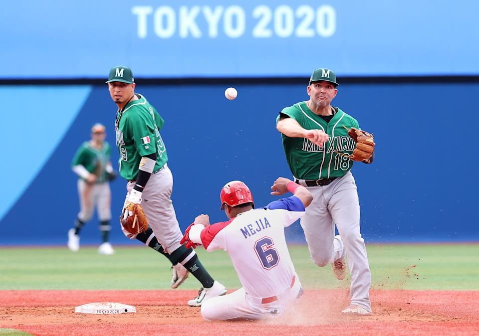 YOKOHAMA, JAPAN - JULY 30: Daniel Espinosa #18 of Team Mexico throws to first base to finish the double play as Erick Mejia Buret #6 of Team Dominican Republic slides into second base too late in the sixth inning during the baseball opening round Group A game on day seven of the Tokyo 2020 Olympic Games at Yokohama Baseball Stadium on July 30, 2021 in Yokohama, Kanagawa, Japan. (Photo by Koji Watanabe/Getty Images)