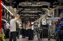 FILE PHOTO: Workers assemble vehicles on the assembly line of the SEAT car factory in Martorell