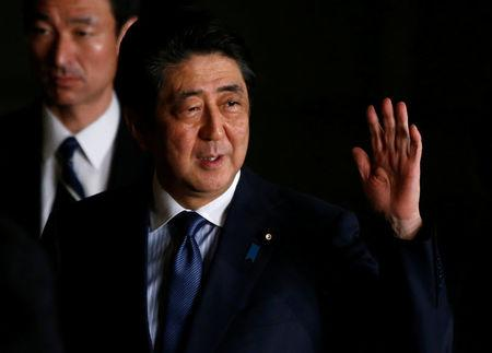 Japan's PM Shinzo Abe raises his hand as he walks at his official residence in Tokyo