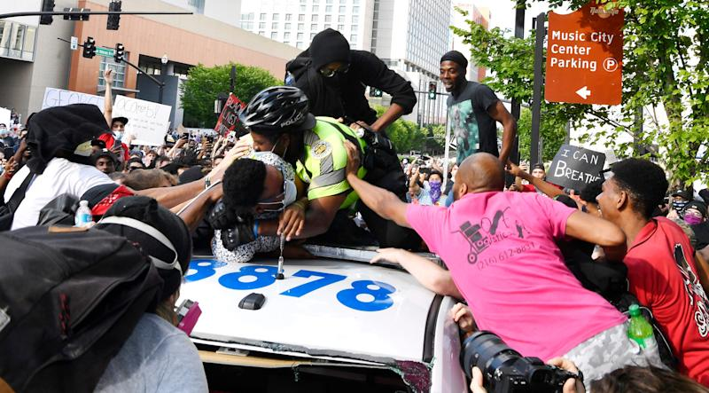 "Protesters and Metro Nashville Police scuffle on top of a police car outside Central Precinct in Nashville, Tenn., Saturday, May 30, 2020 during the ""I Will Breathe"" rally to protest the death of George Floyd, an unarmed black man who died after being pinned down by a white Minneapolis police officer on Memorial Day. (Via OlyDrop)"