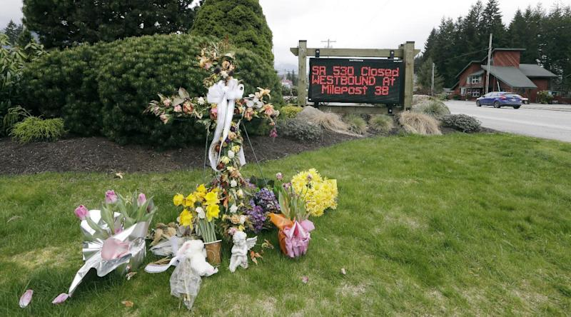 A road sign advising the closure of Highway 530 stands near a small display of flowers and a cross Tuesday, April 15, 2014, in Darrington, Wash. One more victim has been recovered from the mudslide that hit the nearby town of Oso, Wash., March 22, raising the death toll to 37, the Snohomish County medical examiner's office said Tuesday. Seven people remain on the missing list, the sheriff's office said. (AP Photo/Elaine Thompson)