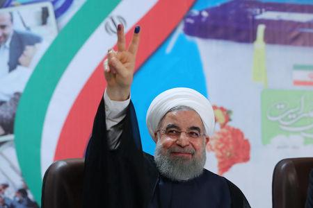 Iran's President Hassan Rouhani gestures as he registers to run for a second four-year term in the May election, in Tehran