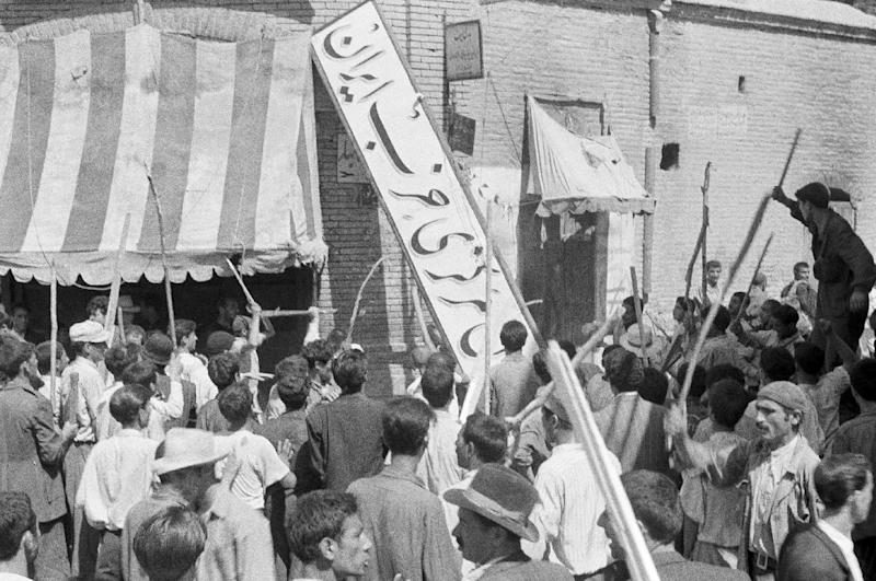 FILE -- In this August 19, 1953 file photo, a crowd of demonstrators tears down the Iran Party's sign from the front of the headquarters in Tehran, Iran, during the pre-Shah riot which swept through the capital and ousted Persian Prime Minister Dr. Mossadegh and his government. On Tuesday, Aug. 27, 2013, Iran's parliament approved fast tracking debate on a bill that seeks to sue the U.S. for its involvement in the 1953 coup that overthrew the country's democratically elected prime minister. Newly declassified documents revealed recently offer more details of how the CIA orchestrated the overthrow of Iranian Prime Minister Mohammed Mossadegh 60 years ago. (AP Photo, File)