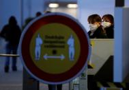 Employees wearing face masks look past a sign promoting safe distancing measures, as Skoda Auto restarts production at its factory following a shutdown last month due to the coronavirus disease (COVID-19) outbreak in Mlada Boleslav