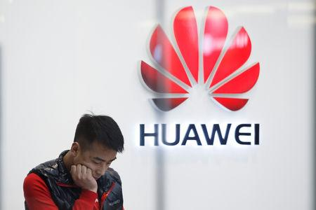 FILE PHOTO:  A staff member stands in front of a Huawei shop in Beijing