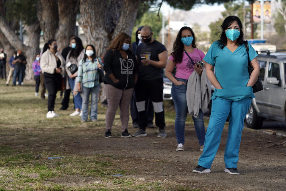 FILE - In this Jan. 13, 2021, file photo, health care workers line up to receive at a COVID-19 vaccination at Ritchie Valens Recreation Center in Pacoima, Calif. California will require all of its roughly 2.2 million health care and long term care workers to be fully vaccinated against the coronavirus by Sept. 30. Gov. Gavin Newsom said last month he would require health care workers to either be vaccinated or submit to weekly testing. But the new order issued Thursday, Aug. 5 by the California Department of Public Health does not give health care workers a choice. (AP Photo/Marcio Jose Sanchez, File)