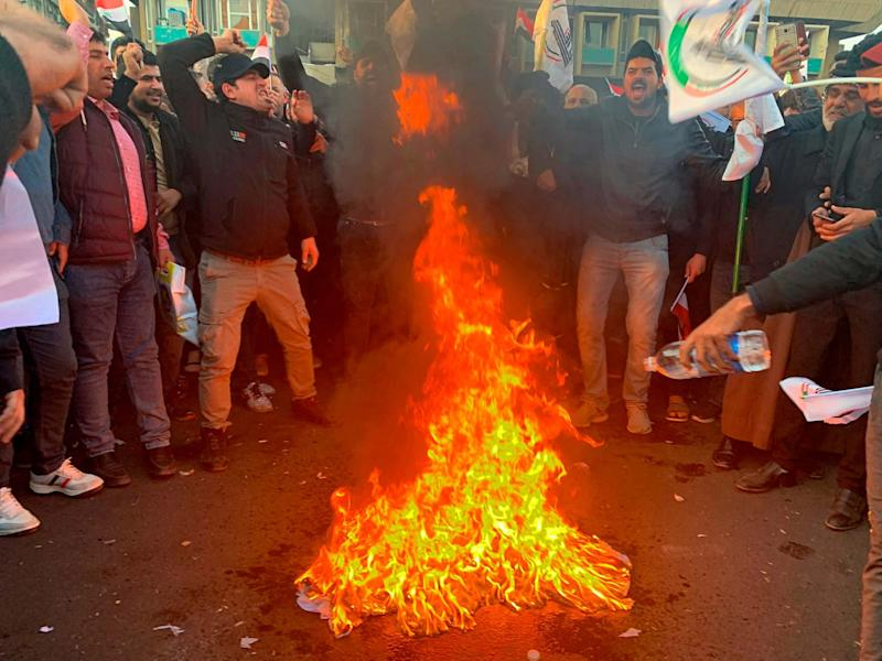 Protesters burn a representation of a US flag during a protest against the airstrikes on Kataeb Hezbollah: AP
