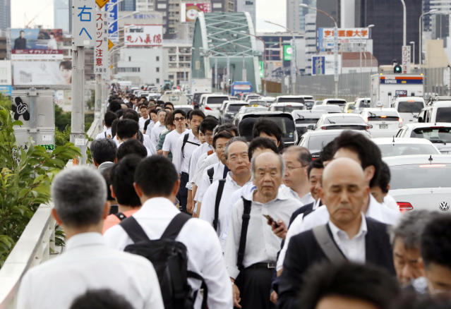 <p>People walk on a bridge while train and subway service were suspended to check for damage after an earthquake in Osaka, western Japan, June 18, 2018. (Photo: Meika Fujio/Kyodo News via AP) </p>