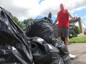 Jeremy Rogers drops bags of household items that were ruined by flood waters from Tropical Storm Ida outside his home in Manville, N.J., on Friday, Sept. 3, 2021. (AP Photo/Wayne Parry)
