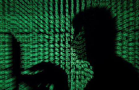 Man holds laptop computer as cyber code is projected on him in this illustration picture