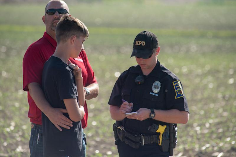A police officer interviews a student and adult.