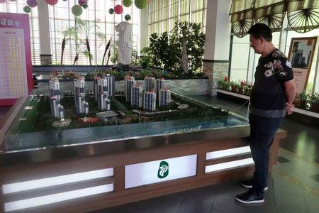 Brothers Holdings Managing Director T.C. Koh stands next to a model of Singapore City inside a property showroom in Dandong, Liaoning province, China