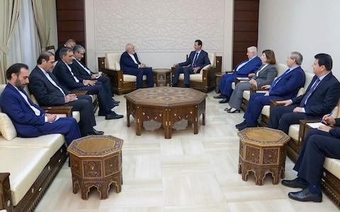 Syrian President Bashar al-Assad, centre right, meets with Iranian Foreign Minister Mohammad Javad Zarif in Damascus, Syria on Monday, - Credit: SANA