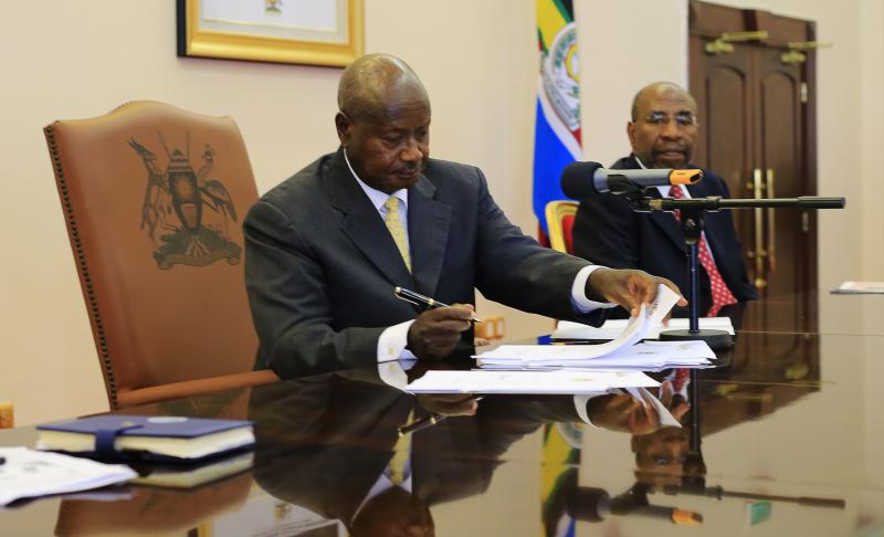Uganda President Yoweri Museveni signs an anti-homosexual bill into law at the state house in Entebbe