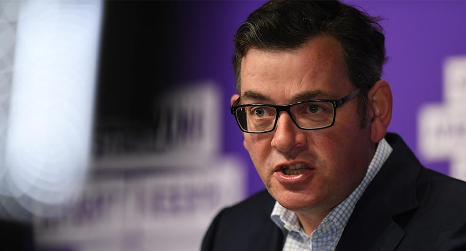 Photo shows Daniel Andrews appearing frustrated at a media conference.