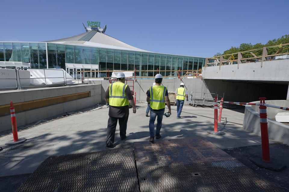 Visitors walk down a ramp outside Climate Pledge Arena during a media tour of the facility, Monday, July 12, 2021, in Seattle. The arena will be the home of the NHL hockey team Seattle Kraken and the WNBA Seattle Storm basketball team as well as hosting concerts and other performing arts events. (AP Photo/Ted S. Warren)