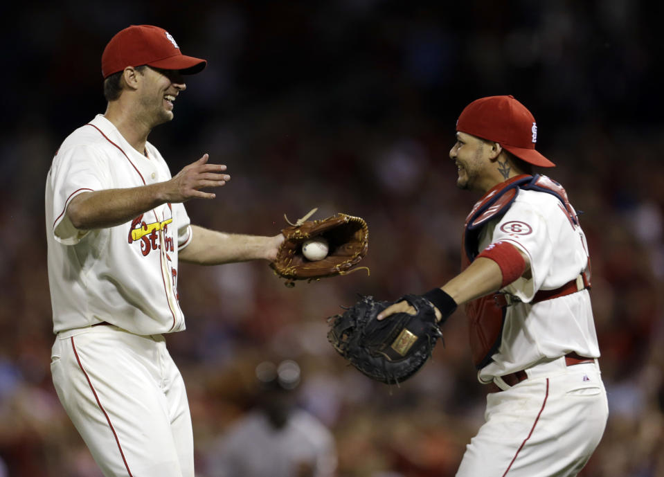 St. Louis Cardinals starting pitcher Adam Wainwright, left, is congratulated by catcher Yadier Molina after throwing a complete baseball game against the San Francisco Giants in the second game of a doubleheader on Saturday, June 1, 2013, in St. Louis. The Cardinals won 7-1. (AP Photo/Jeff Roberson)