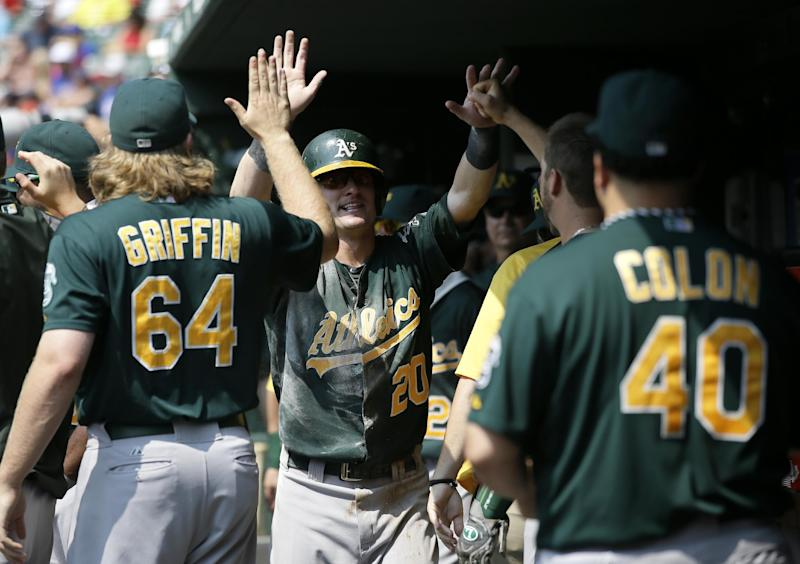 Oakland Athletics' A.J. Griffin (64) and Bartolo Colon (40) congratulate Josh Donaldson (20) after Donaldson scored on an RBIdouble by Brandon Moss in the first inning of a baseball game against the Texas Rangers, Saturday, Sept. 14, 2013, in Arlington, Texas. (AP Photo/Tony Gutierrez)