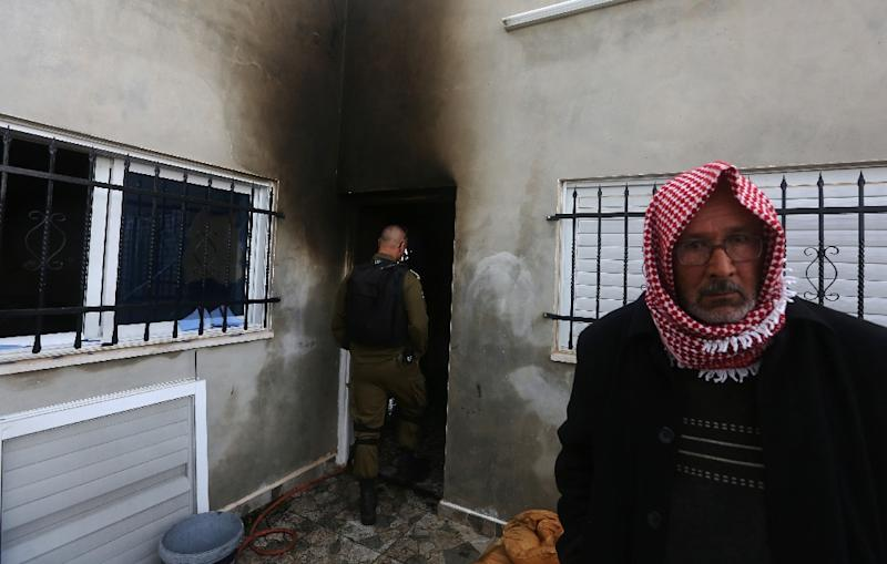 A Palestinian man stands outside a burnt-out house belonging to a key witness to an arson attack carried out last year by Jewish extremists that killed a Palestinian family, in the Israeli-occupied West Bank village of Duma, on March 20, 2016 Residents reported that a window was broken in the house, raising suspicions that Molotov cocktails were thrown inside -- as occurred in the July firebombing. Israeli authorities were investigating the cause of the fire. This is the second attack to take place in the village, where an 18-month-old Palestinian boy and his two parents from the Dawabsha family were killed in the July 2015 firebombing. Dawabsha and his wife were awakened overnight by thick smoke, residents said. In January, a court charged two Israelis over the firebombing after slow progress in the case led to criticism from rights groups and Palestinians. (AFP Photo/Jaafar Ashtiyeh)