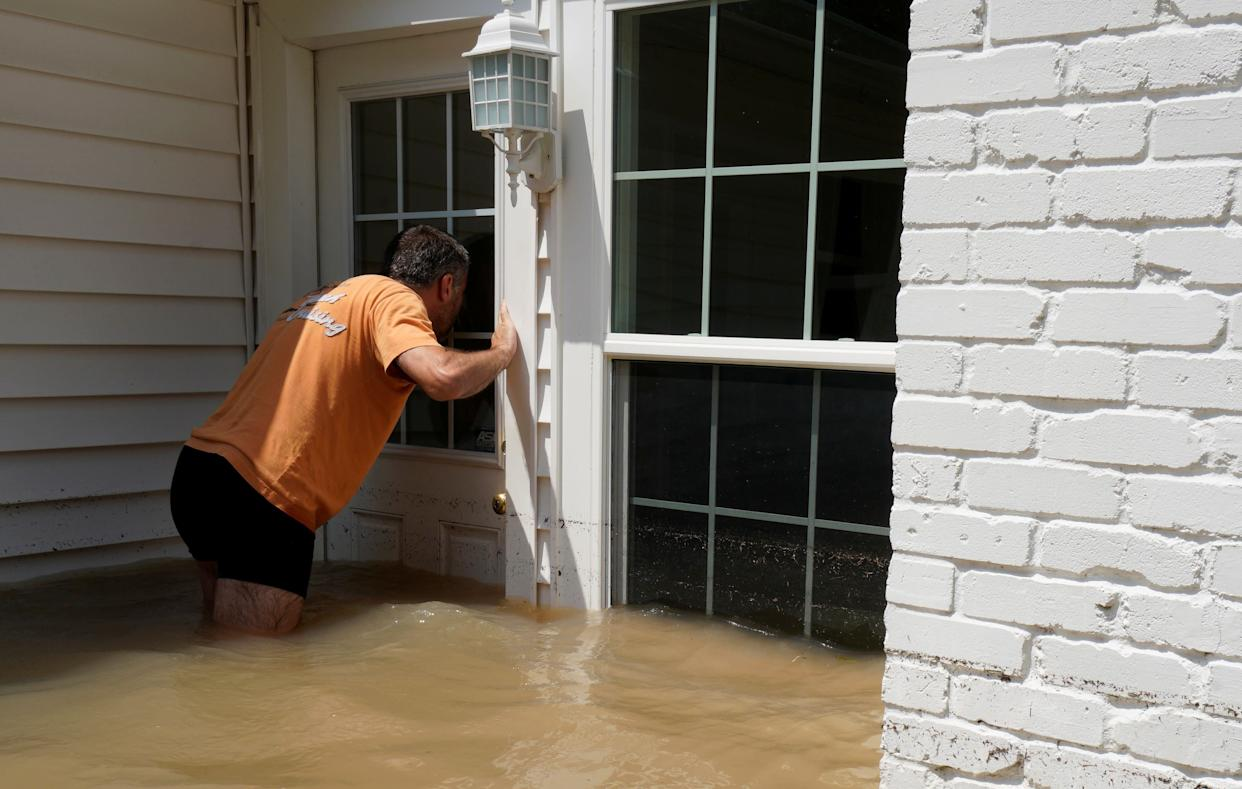 Patrice Laporte looks to see how much water is in his house on Sept. 1.
