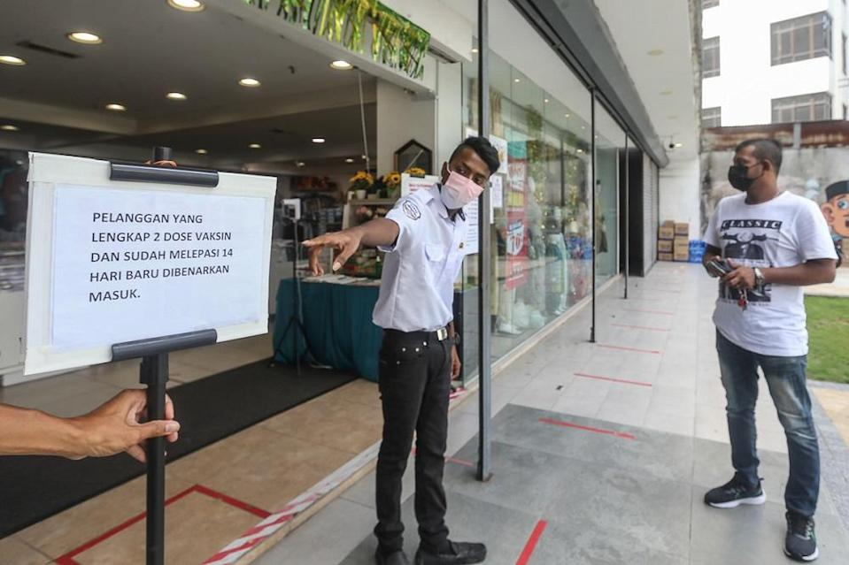 A security personnel points at a notice informing customers of Covid-19 vaccination requirements at a shop in Kuala Lumpur August 17, 2021. — Picture by Yusof Mat Isa