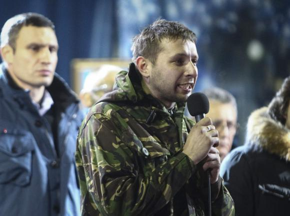 Anti-presidential protester Volodymyr Parasiuk addresses the crowd as opposition leader Vitaly Klitschko (L) looks on during a rally in Kiev February 21, 2014. When the history of the bloody turbulence in Ukraine is written, 26-year-old Parasiuk who learned combat skills in the army cadets may be recorded as the man who made up Viktor Yanukovich's mind to cut and run. To match Insight UKRAINE-CRISIS/HERO   Picture taken February 21, 2014.  REUTERS/Vitaliy Nosach (UKRAINE - Tags: POLITICS CIVIL UNREST PROFILE)