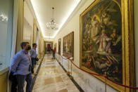 Visitors look at paintings in the Papal Palace in Castel Gandolfo, some 30 kilometers southeast of Rome, Saturday, May 29, 2021. As Covid-19 restrictions are slowly being lifted in Italy, thousands of people are returning to visit the extensive gardens and apartments at the Papal Palace of Castel Gandolfo in the Alban Hills near Rome, that for hundreds of years have been the summer retreat for Popes seeking to escape the suffocating heat of Rome. (AP Photo/Andrew Medichini)