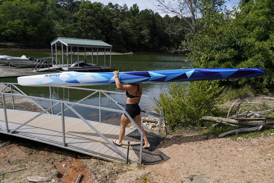 Canoe sprint world champion Nevin Harrison, 19, of Seattle, walks on the deck to train near Lake Lanier Olympic Park on Thursday, July 1, 2021, in Gainesville, Ga. Harrison won the world championship in the women's sprint canoe 200 meters as a 17-year-old in 2019. Now she'll try to duplicate that at the Olympics in Tokyo where the race will be a new event in a bid for gender equity. (AP Photo/Brynn Anderson)