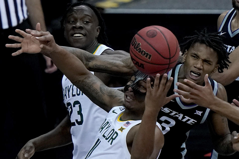 Baylor's Jonathan Tchamwa Tchatchoua (23) and Mark Vital (11), along with Kansas State's DaJuan Gordon (3), battle for a loose ball during the second half of an NCAA college basketball game in the second round of the Big 12 Conference tournament in Kansas City, Mo., Thursday, March 11, 2021. (AP Photo/Charlie Riedel)