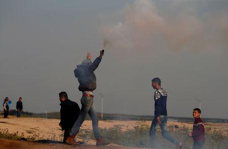 A Palestinian demonstrator holds a tear gas canister fired by Israeli troops during a protest at the Israeli-Gaza border fence, east of Gaza City March 29, 2019. REUTERS/Mohammed Salem