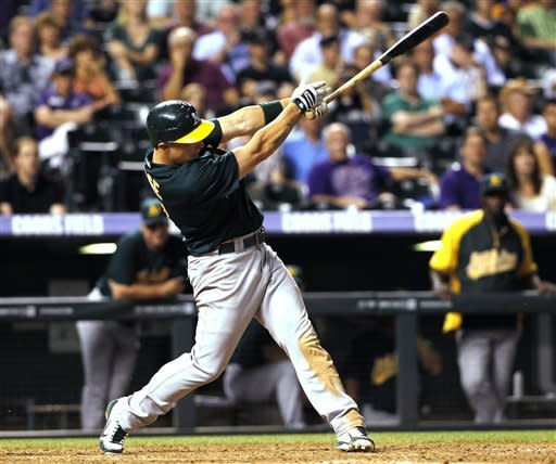 Oakland Athletics' Brandon Inge follows through with his swing after hitting a double to drive in the go-ahead runs against the Colorado Rockies in the ninth inning of the Athletics' 10-8 victory in a interleague baseball game in Denver on Wednesday, June 13, 2012. (AP Photo/David Zalubowski)