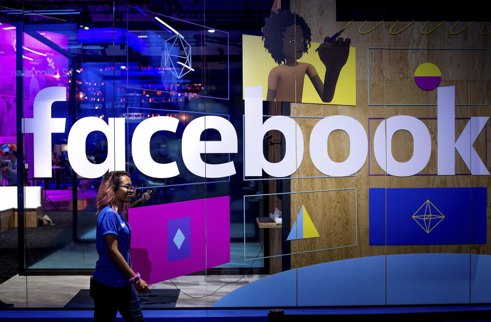 FILE - In this Tuesday, April 18, 2017, file photo, a conference worker passes a demo booth at Facebook's annual F8 developer conference, in San Jose, Calif.  New York Attorney General Letitia James says a bipartisan coalition of state attorneys general is investigating Facebook for alleged antitrust issues. James said Friday, Sept. 6, 2019 the probe will look into whether Facebook's actions endangered consumer data, reduced the quality of consumers' choices or increased the price of advertising.   (AP Photo/Noah Berger, File)