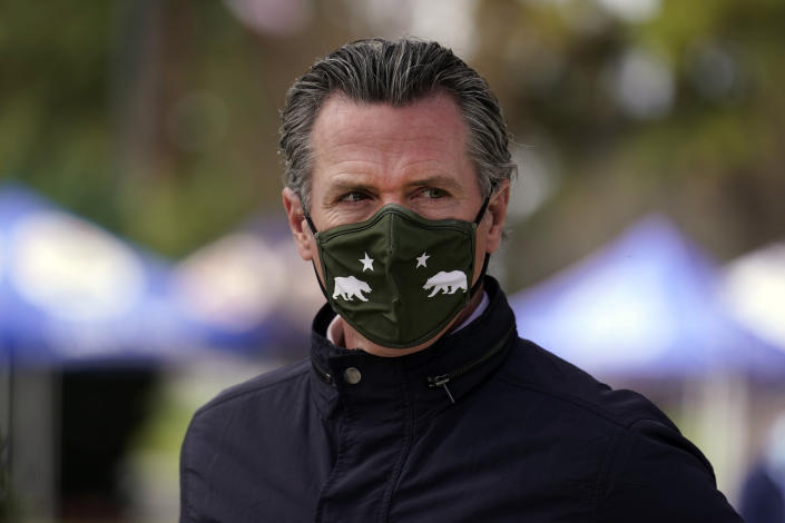 """FILE - In this March 10, 2021, file photo, California Gov. Gavin Newsom wears a mask during a visit to a vaccination center in South Gate, Calif. Gov. Newsom said Tuesday, May 11, 2021, the nation's most populous state would stop requiring people to wear masks in almost all circumstances on June 15, describing a world he said will look """"a lot like the world we entered into before the pandemic."""" (AP Photo/Marcio Jose Sanchez, File)"""