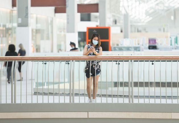 A woman wears a face mask as she looks on at an open shopping mall in Montreal on June 20, 2020.