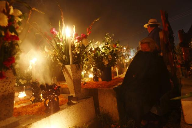 A woman pays her respects at the graves of her relatives in San Andres cemetery, Mixquic. (Reuters)