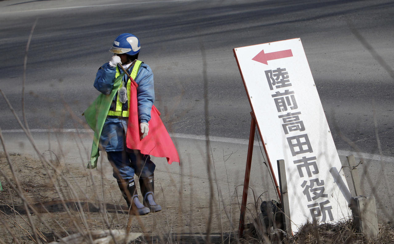 """In this Friday, Feb. 22, 2013 photo, standing by a signboard reading: """"Rikuzentakata City Hall,"""" a worker holds flags to control traffic under cold weather in a street near a new road construction site in Rikuzentakata, Iwate Prefecture. Japan's progress in rebuilding from the tsunami that thundered over coastal sea walls, sweeping entire communities away, is mainly measured in barren foundations and empty spaces. Clearing of forests on higher ground due to be leveled to make space for relocating survivors has barely begun. Japan next week, will observe two years from the March 11, 2011 disasters which devastated in the northeastern Pacific coast of the country. (AP Photo/Junji Kurokawa)"""