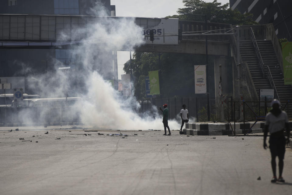 Protesters run away as police officers use teargas to disperse groups demonstrating against police brutality in Lagos, Nigeria, Wednesday Oct. 21, 2020. After 13 days of protests against alleged police brutality, authorities have imposed a 24-hour curfew in Lagos, Nigeria's largest city, as moves are made to stop growing violence. ( AP Photo/Sunday Alamba)