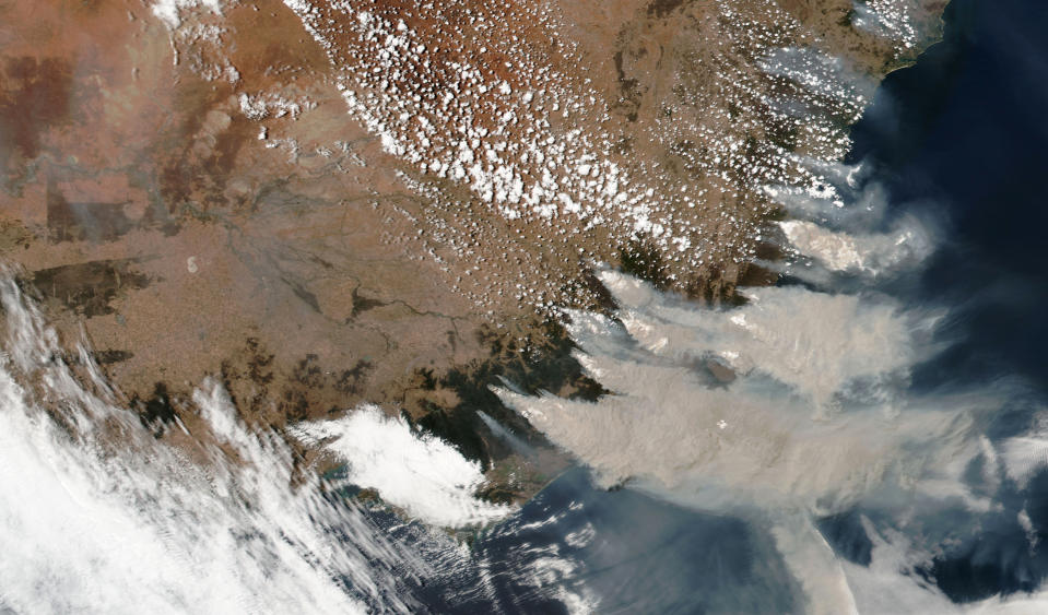 This satellite image provided by NASA on Saturday, Jan. 4, 2020 shows wildfires in Victoria and New South Wales, Australia.  Australia's prime minister called up about 3,000 reservists on Saturday as the threat of wildfires escalated in at least three states, while strong winds and high temperatures were forecast to bring flames to populated areas including the suburbs of Sydney. (NASA via AP)