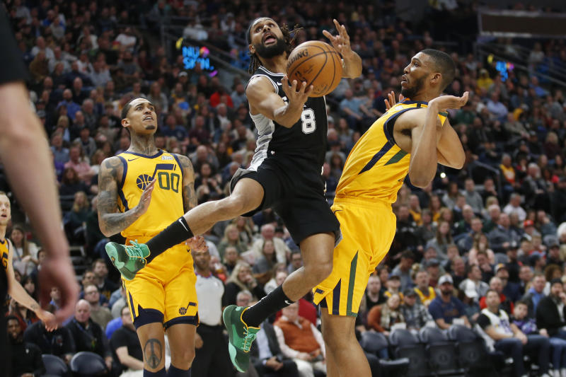 San Antonio Spurs guard Patty Mills (8) lays the ball up as Utah Jazz's Jordan Clarkson (00) and Tony Bradley, right, defend during the first half of an NBA basketball game Friday, Feb. 21, 2020, in Salt Lake City. (AP Photo/Rick Bowmer)