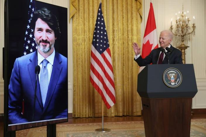 U.S. President Joe Biden gestures to Canada's Prime Minister Justin Trudeau, appearing via video conference call, during closing remarks at the end of their virtual bilateral meeting from the White House in Washington