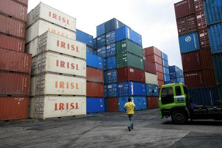 A truck driver walks past a stack of IRISL containers at a depot in northern Singapore