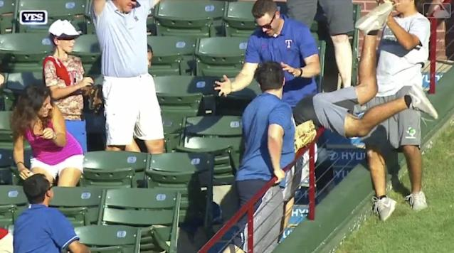A Yankees fan toppled over a railing while catching a Neil Walker home run during the Yankees-Rangers game at Globe Life Park. (MLB.com)