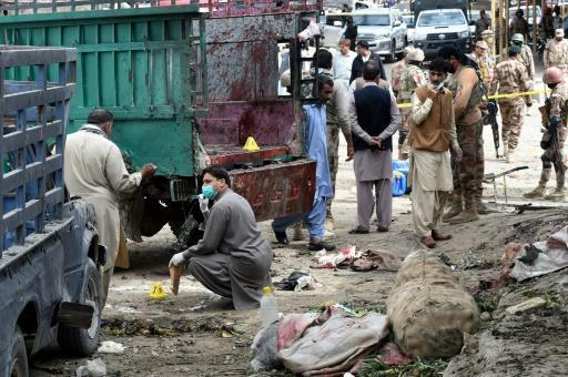 Pakistani security officials inspect the site of a bomb blast at a fruit market in Quetta