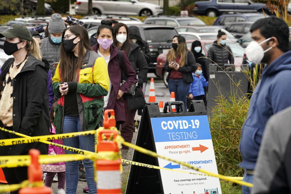 FILE - In this Nov. 18, 2020, file photo, people line up to be tested for the coronavirus at a free testing site in Seattle. With coronavirus cases surging and families hoping to gather safely for Thanksgiving, long lines to get tested have reappeared across the U.S. (AP Photo/Elaine Thompson, File)