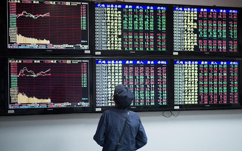 An elderly investor looks at stock prices at a securities exchange in Shanghai on August 22, 2014