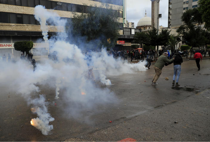 Protesters run from tear gas canisters during a protest against deteriorating living conditions and strict coronavirus lockdown measures, in Tripoli, north Lebanon, Thursday, Jan. 28, 2021. Violent confrontations between protesters and security forces over the last three days in northern Lebanon left a 30-year-old man dead and more than 220 people injured, the state news agency said Thursday. (AP Photo/Hussein Malla)