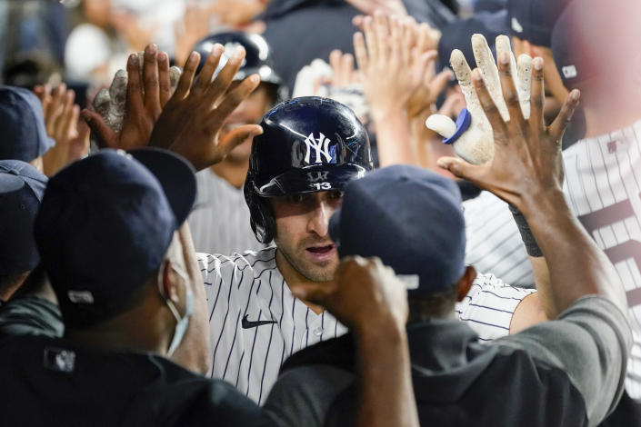New York Yankees' Joey Gallo is congratulated by teammates after his three-run home run during the seventh inning of the team's baseball game against the Seattle Mariners, Thursday, Aug. 5, 2021, in New York. (AP Photo/Mary Altaffer)
